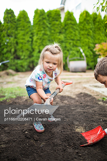 Brother and sister shoveling dirt in backyard, landscaping project - p1166m2208471 by Cavan Images