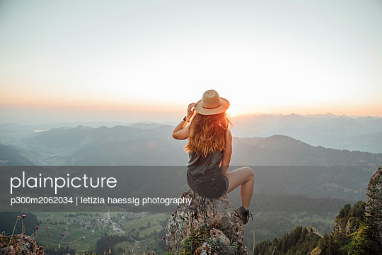 Switzerland, Grosser Mythen, young woman on a hiking trip sitting on a rock at sunrise - p300m2062034 by letizia haessig photography