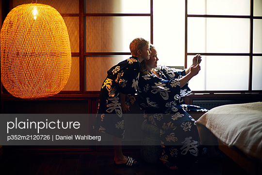 Mother and daughter wearing kimonos taking selfie - p352m2120726 by Daniel Wahlberg