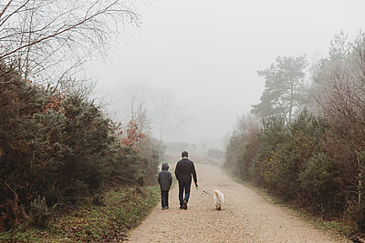 Rear view of father and son walking dog along gravel path in fog - p1166m2258283 by Cavan Images