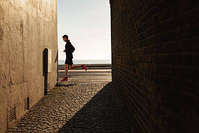 Mann running through city - p1477m2038923 by rainandsalt