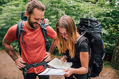 Happy young couple on a hiking trip reading map - p300m1587665 von Gustafsson