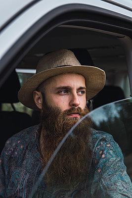 Bearded young man looking out of car window - p300m2060845 by Kike Arnaiz