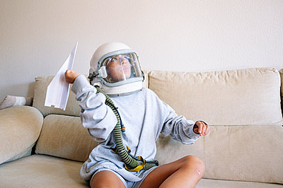 Boy wearing space helmet flying paper airplane while sitting on sofa at home - p300m2221333 by Jose Luis CARRASCOSA