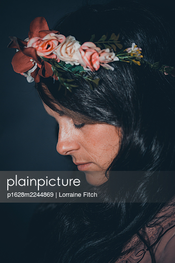 Dark haired woman with floral wreath in her hair - p1628m2244869 by Lorraine Fitch