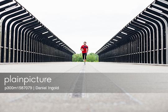 Man running on a bridge - p300m1587079 von Daniel Ingold
