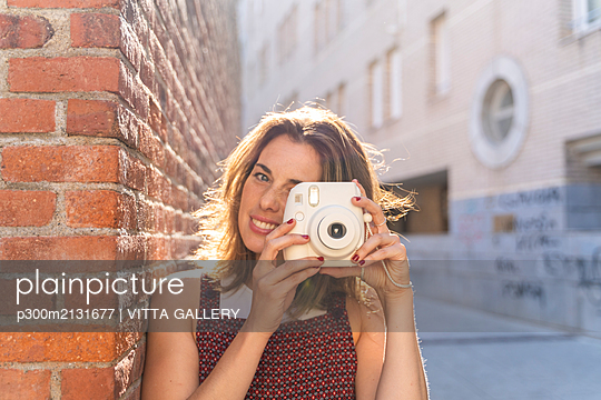 Young woman leaning on brick wall, using camera - p300m2131677 by VITTA GALLERY