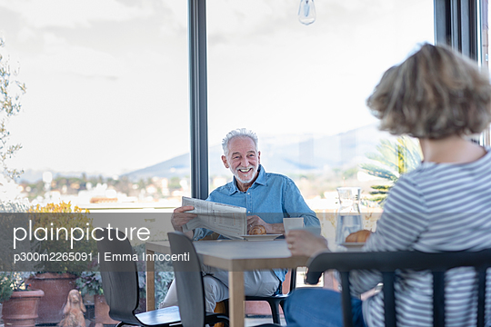 Smiling man with newspaper looking at woman while sitting at home - p300m2265091 by Emma Innocenti