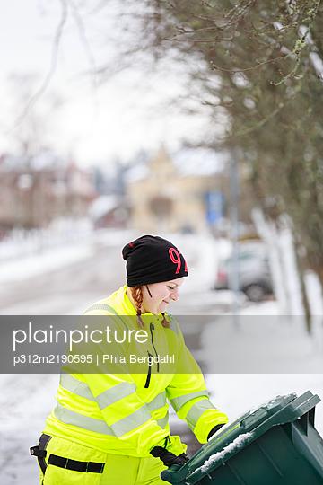 Woman pushing dustbin - p312m2190595 by Phia Bergdahl
