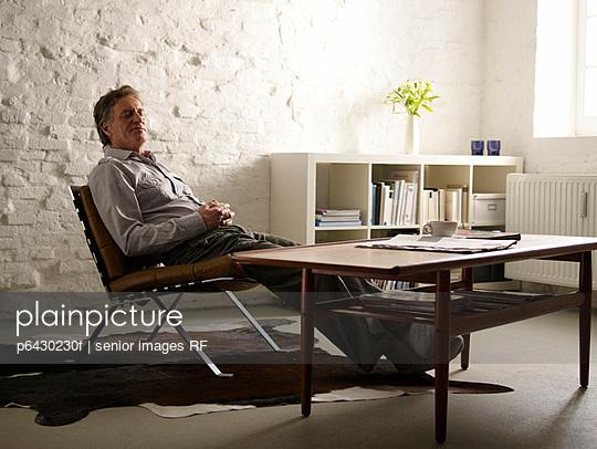 Aelterer Mann entspannt auf einem Sessel  - p6430230f von senior images RF