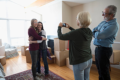 Parents with camera phone photographing lesbian couple moving into new house - p1192m1560012 by Hero Images