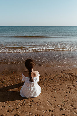 Girl looks at the sea sitting on the beach - p1623m2290980 by Donatella Loi