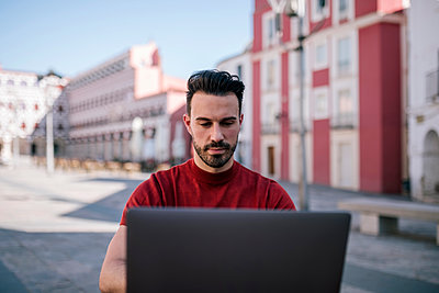 Handsome man using laptop in city - p300m2202664 by LUPE RODRIGUEZ