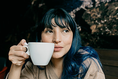 Beautiful woman having coffee while looking away - p300m2274483 by MORNINGVIEW AGENCY