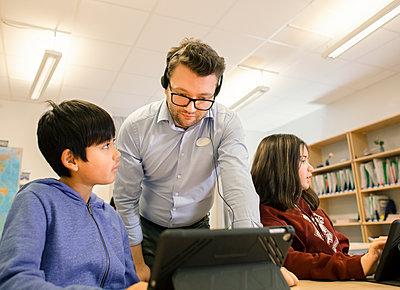 Teacher with schoolboy in classroom - p312m2174776 by Scandinav