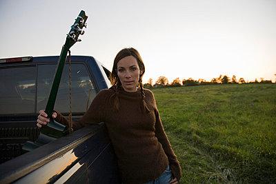 Woman holding guitar - p4296270 by Hugh Whitaker