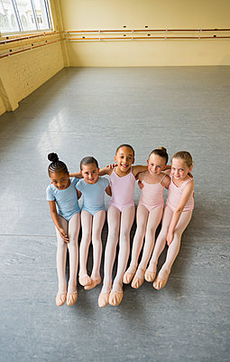 Portrait of smiling girls hugging on floor of ballet studio - p555m1491103 by Mark Edward Atkinson
