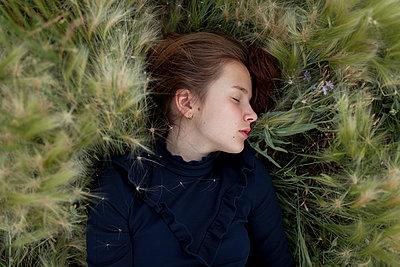 Caucasian girl laying in field - p555m1521418 by Vyacheslav Chistyakov
