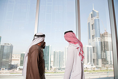 Middle eastern businessmen looking at dubai through office window - p9244778f by Image Source