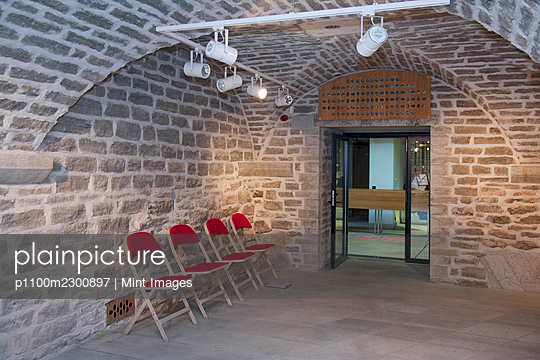 Chairs in a vaulted stone room for lectures meetings or seminars at a university - p1100m2300897 by Mint Images