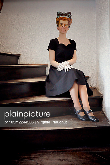 Woman in black dress and mask in the stairwell - p1105m2244906 by Virginie Plauchut