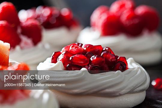 Meringue pastry garnished with whipped cream and pomegranate seed - p300m1587345 von Dieter Heinemann