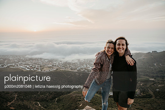 South Africa, Cape Town, Kloof Nek, portrait of two happy women embracing at sunset - p300m2081048 by letizia haessig photography