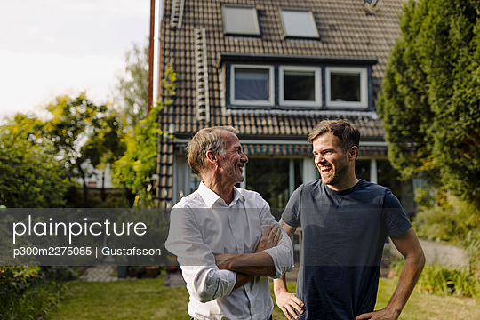 Smiling father with arms crossed looking at cheerful son while standing in backyard - p300m2275085 by Gustafsson