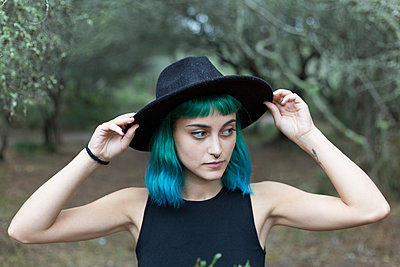 Portrait of young woman with dyed blue and green hair wearing black hat on rainy day - p300m2120813 by Sus Pons