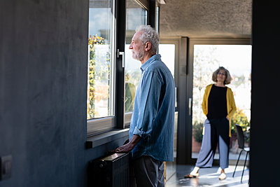 Senior man looking through window while standing with woman in background at home - p300m2265850 by Emma Innocenti