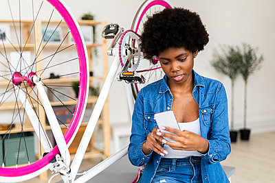 Young woman using mobile phone while sitting by bicycle on table at home - p300m2275982 by Giorgio Fochesato