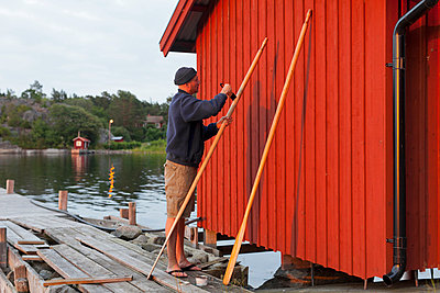 Man painting oar - p312m799067f by Conny Fridh