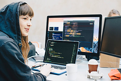Side view of female computer programmer looking away while using laptop at desk in office - p426m1493995 by Maskot