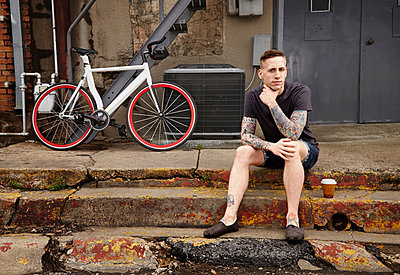 Portrait of young tattooed man on steps - p429m802533 by Cultura