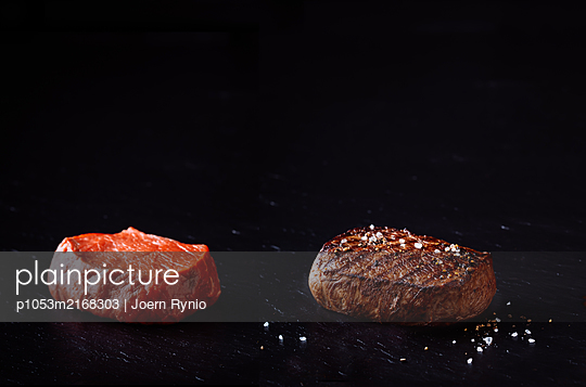 Grilled beef steak and raw beef steak isolated on black background - p1053m2168303 by Joern Rynio