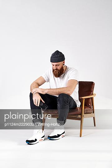 Mann mit Vollbart und Handy sitzt in einem Sessel - p1124m2229032 von Willing-Holtz