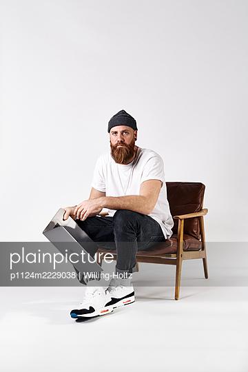 Mann mit Laptop im Sessel - p1124m2229038 von Willing-Holtz