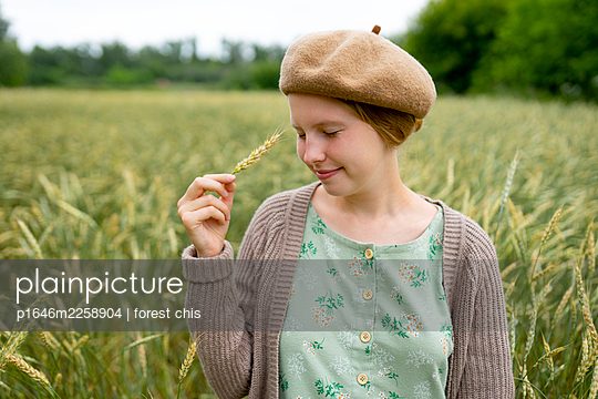 Woman touching her face with corn ear, portrait - p1646m2258904 by Slava Chistyakov