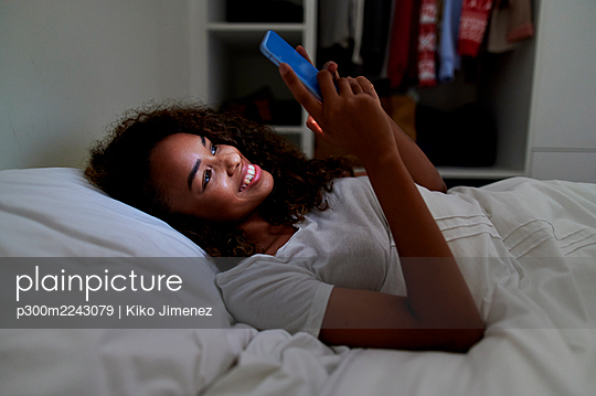 Happy young woman using smart phone while lying on bed in bedroom at home - p300m2243079 by Kiko Jimenez
