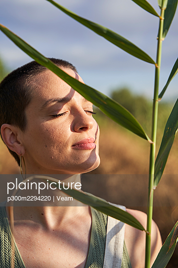 Young woman eyes closed holding leaves on sunny day - p300m2294220 by Veam