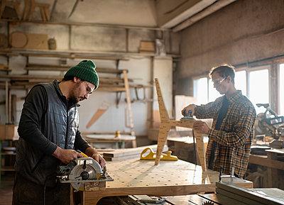 Male carpenters working in workshop - p1166m2285656 by Cavan Images