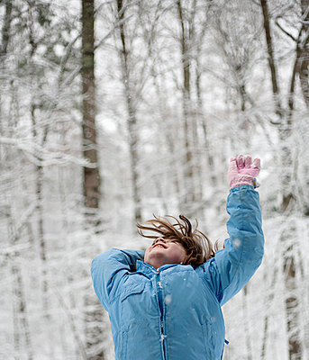 Girl throwing snow in the woods - p300m1068996f by Candina Maria