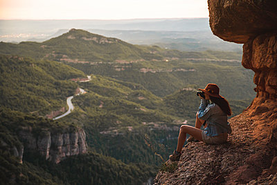 Young woman on a hiking trip wearing a hat sitting on a rock taking a picture - p300m2041577 by VITTA GALLERY