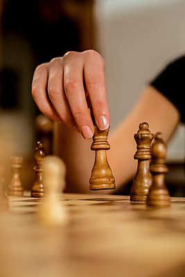 Close-up of a woman's hand moving a chess piece - p300m2078665 von Aitor Carrera Porté