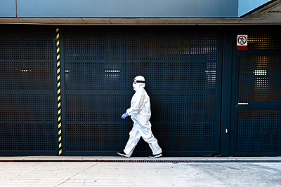 Female scientist wearing protective suit and mask and walking in front of a wall - p300m2170099 by Eloisa Ramos