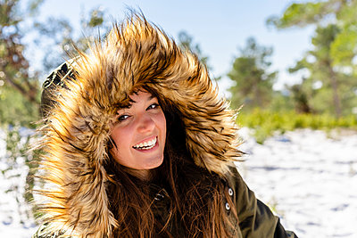 Smiling young woman wearing fur hooded winter coat staring while standing in forest - p300m2250942 by Javier De La Torre Sebastian