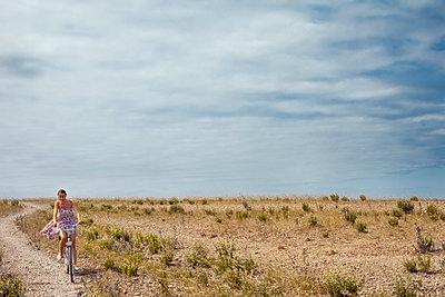 Sweden, Oland, Byxelkrok, Woman cycling across  field - p352m1186849 by Jezzica Sunmo
