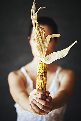 Woman holding corn cob in Hands - p968m2020210 by roberto pastrovicchio