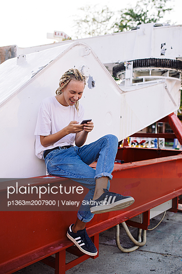 Smiling teenager boy with dreadlocks is using mobile phone - p1363m2007900 by Valery Skurydin