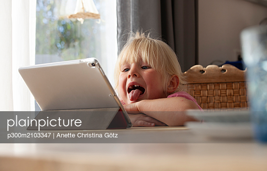 Portrait of blond little girl sticking out tongue while looking at digital tablet - p300m2103347 by Anette Christina Götz